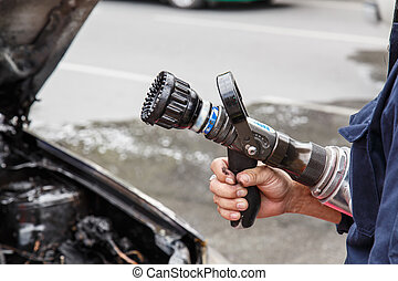 Hand holding water hose to prevent fire on car