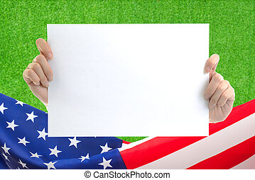 Hand holding white blank paper sheet mockup with US flag border on green grass background