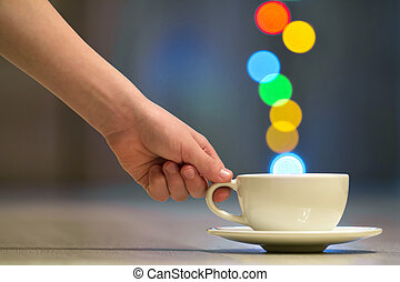 Hand holding white cup of coffee with colorful bokeh steam