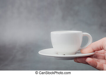 Hand holding white cup of coffee with saucer on dark background