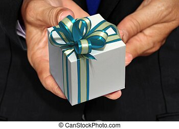 Hand holding white gift box with blue ribbon