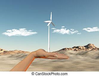 Hand holding wind turbine against a desert