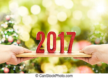 Hand holding wood plate with 2017 new year red glitter...