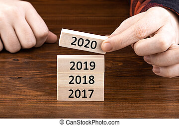 hand holding wooden cube with flip over block 2019 to 2020 word on table background. Resolution, strategy, solution, goal, business, New Year New You and happy holiday concepts