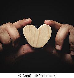 holding wooden heart