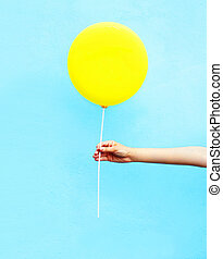 Hand holding yellow air balloon over colorful blue ...