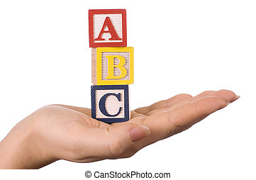 Hand holds a cube with letters