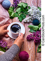 Hand holds a cup of morning coffee with spring lilac flowers branches blossoming on wooden background view from above. Flat lay underground style.