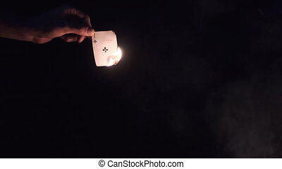Hand Holds Burning Card on Black Background near Campfire on Nature. Game card in fire at night. Ignited ace cross near tongues of flame and smoke. The ritual burning of game card. Slow motion