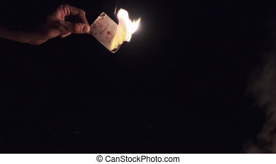 Hand Holds Burning Card on Black Background near Campfire on Nature. Game card in fire at night. Ignited ace of diamonds near tongues of flame and smoke. The ritual burning of game card. Slow motion