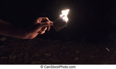 Hand Holds Burning Card on Black Background near Campfire on Nature. Game card in fire at night. Ignited jack of hearts near tongues of flame and smoke. The ritual burning of game card. Slow motion