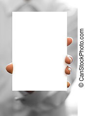 hand holds white blank business card in focus