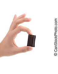 Hand holds chocolate bar. Close up. White background.