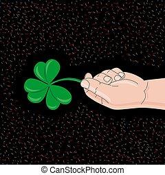 Hand holds clover on black background. St. Patrick Day Symbol