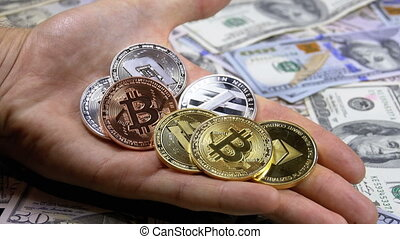 Hand Holds Different Coins of Cryptocurrency on a Table with US Dollars are Rotating