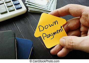 Hand holds Down Payment inscription near desk.