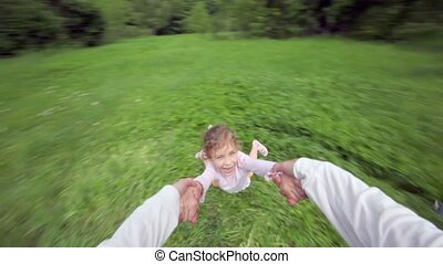 Hand holds girl which flies above grass and brother runs around