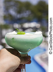 Hand holds green cocktail in a beautiful glass with ice cream and green mint leaves