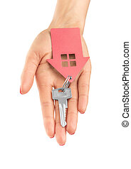 Hand holds key with a keychain the shape of house.