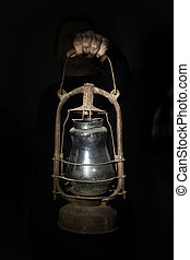 Hand holds old lamp