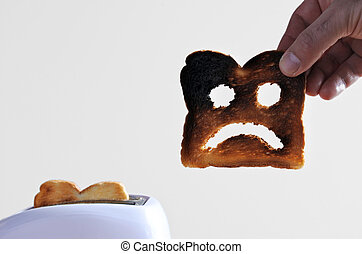 Hand holds one slices of burnt toast bread with sad face...