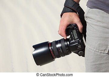 hand holds photo camera and sand