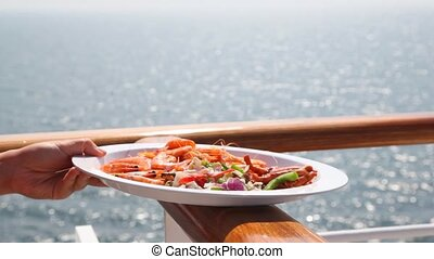 hand holds plate with seafood and salad on handrail against...