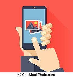 Hand holds smartphone with photos