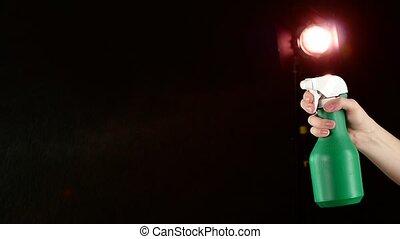 Hand holds spray bottle, on black, slow motion, back light