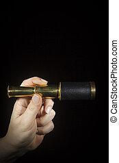 Hand holds spyglass
