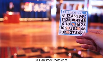 hand holds ticket for game in bingo and leader declares figures