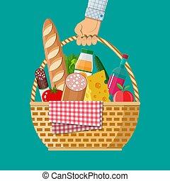 Hand holds wIcker picnic basket full of products.