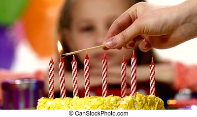 Hand ignites red candle on yellow cake, the girl in the back. Rasfokus. on the table there are gifts