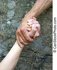 Hand in a hand on a background a rock...