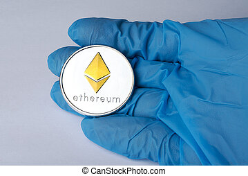 Hand in blue glove holding a silver Ethereum.
