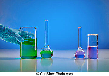 Hand in disposable glove holding beaker, green liquid. Medical flasks, purple chemical reagents, blue background. Coronavirus, pandemic COVID-19