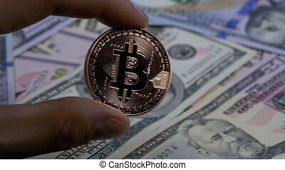 Hand in Fingers Holds a Bronze Coin Bitcoin, BTC on a Background with Bills of Dollars