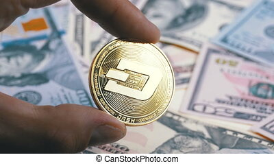 Hand in Fingers Holds a Gold Coin Dash on a Background with Bills of Dollars