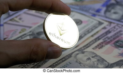 Hand in Fingers Holds a Gold Coin Ethereum, ETH on a Background with Bills of Dollars