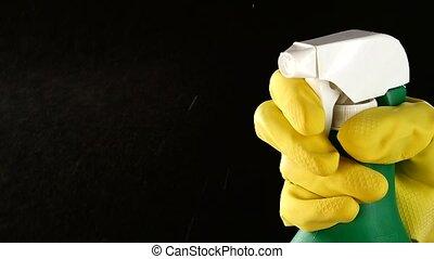 Hand in glove holds spray bottle, on black, slow motion,...