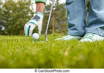 Hand in glove placing golf ball on tee