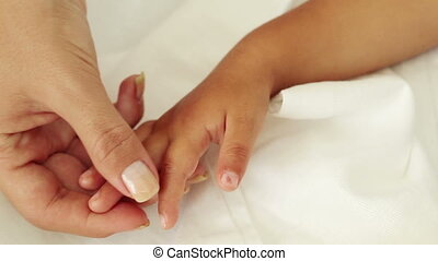 Hand in hand - Mother touching the hand of her child with...