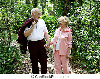 Hand In Hand - An adorable senior couple walking through the...