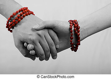 Hand in Hand - hand in hand with red bracelet in white...