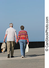 Hand In Hand - Rear view of an elderly couple walking...