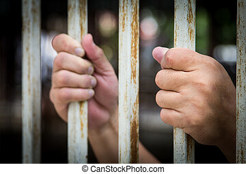 hand in jail - Man's hand holding the bars on both sides.