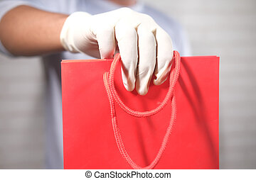 hand in latex gloves holding red color shopping bag on white background
