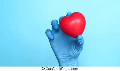 hand in latex gloves holding red heart on blue