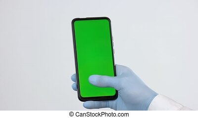 Hand in medical glove using smartphone with green screen. Close up person in latex gloves can not unlock mobile phone. Coronavirus pandemic period.