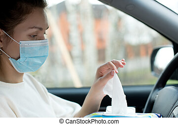 hand in medical mask pulls an antiseptic wipe from a pack while sitting in a car